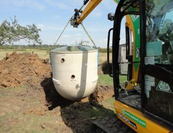 Sewage treatment plant being lowered into excavation
