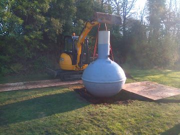 septic tank lowered into excavation