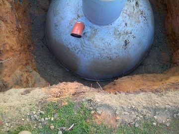 septic tank surrounded in concrete to anchor in place
